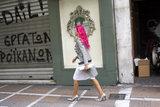 A woman with pink hair walks on the sidewalk / Γυναίκα με ροζ μαλλιά περπατάει στο πεζοδρόμιο