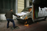 Man tries to extinguish a fire in a car during the brief collisions between the police and students on December 6, 2008  in central Athens on December 6, 2012  /  Ανδρας προσπαθεί να σβήσει φωτιά σε αυτοκίνητο εταιρείας ασφαλείας κατά την διάρκεια σύντομων συγκρούσεων μαθητών με την Αστυνομία