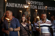 Workers at public hospitals hold lit torches standing infront a banner that reads  - Ministry of unfulfilled commitments - during a protest outside the Finance Ministry, in Athens on the evening of June 15, 2017. The workers are going to spend the night at the Ministry entrance protesting spending cuts in health care. /  Ολονύκτια διαμαρτυρία της ΠΟΕΔΗΝ έξω από το υπουργείο Οικονομικών. Πέμπτη 15 Ιουνίου 2017