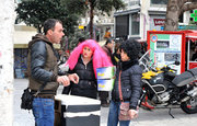 Women wearing carnival wigs watch a street vendor, downtown Athens, Greece, 2013 / Γυναίκες που φορούν αποκριάτικες περούκες παρακολουθούν μικροπωλητή, Αθήνα, 2013
