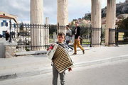 Boy playing the accordion in front of the entrance to the ancient Roman Agora, Plaka area, located under Acropolis hill , Athens, Greece, February 2017 / Αγόρι παίζει ακορντεόν μπροστά από την είσοδο της αρχαίας Ρωμαϊκής Αγοράς, Πλάκα, Αθήνα, Φεβρουάριος 2017